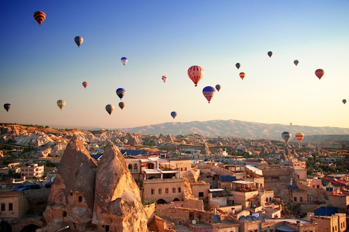 Sunrise in Cappadocia, Turkey, with balloons and typical fairy chimney